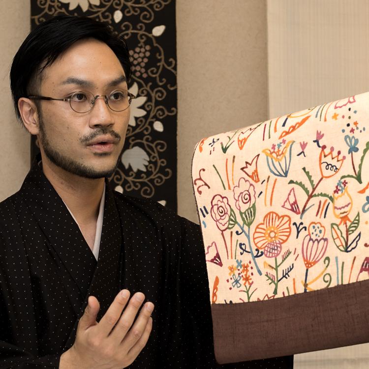 関美穂子さん別注の型染帯「花園」と作品担当 井上英樹
